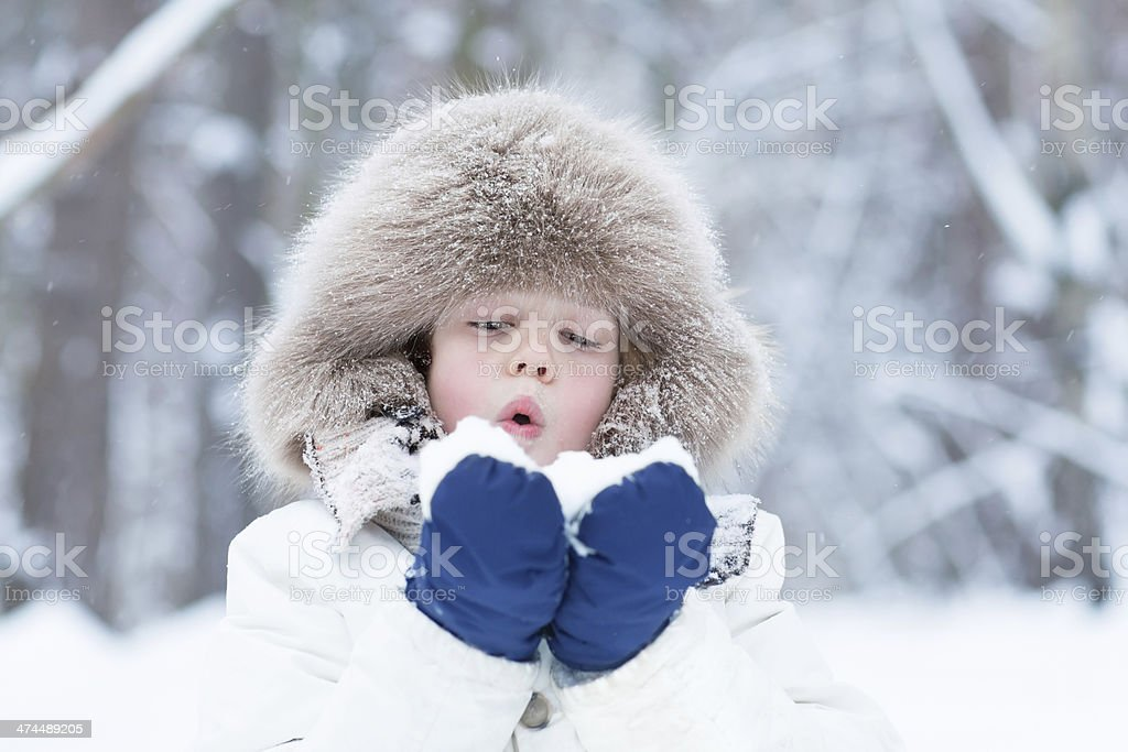 Cute child playing with snow in a winter park stock photo