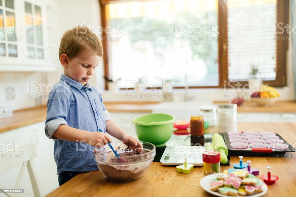 Cute child preparing food in kitchen by standing on chair royalty-free stock photo