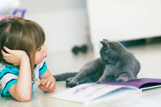 Niedliches Kind, das ein Buch mit seiner Katze liest – Foto