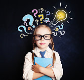 istock Cute child schoolgirl at the blackboard with lightbulb and colorful question marks. Problem and solution. Ideas concept 1019220370