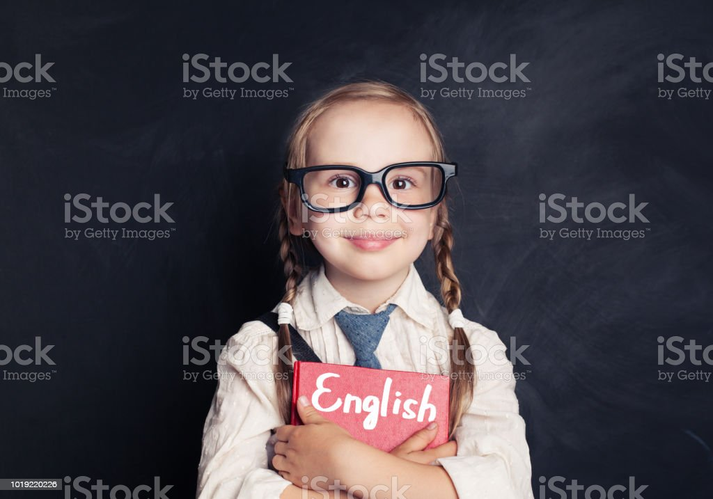 Cute child schoolgirl holding red book on chalkboard background....
