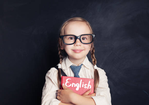 cute child schoolgirl holding red book on chalkboard background. speak english and learn language concept - english foto e immagini stock