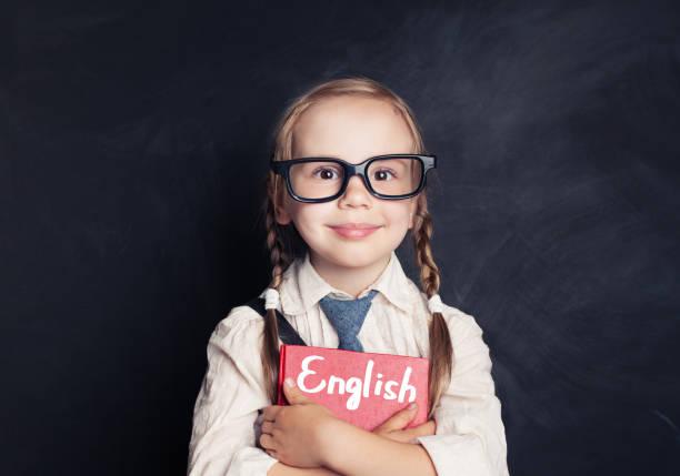 écolière mignon enfant tenant un livre rouge sur fond noir. parler anglais et apprendre le concept de langage - langue anglaise photos et images de collection