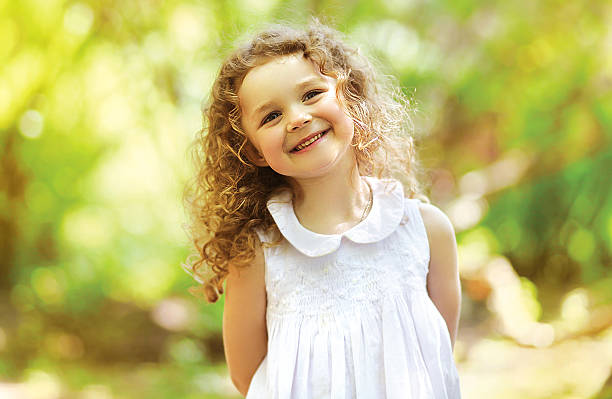 Cute child shone with happiness, curly hair, charming smile stock photo