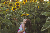 Cute and lovely toddler girl having fun in sunflower field in summer.
