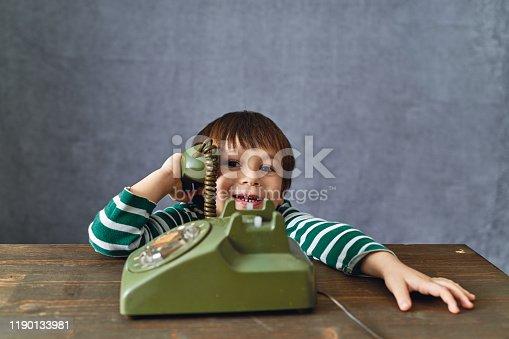 Cute child using phone retro style. 2-3 years child talking on retro style phone.