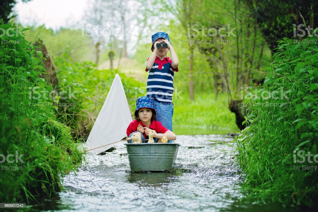 Cute children, boy brothers, playing with boat and ducks on a little river, sailing and boathing. Kid having fun, childhood happiness concept stock photo