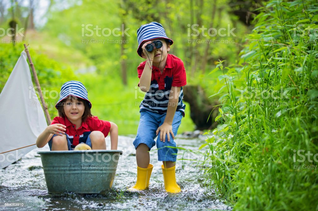 Cute children, boy brothers, playing with boat and ducks on a little river, sailing and boating. Kids having fun, childhood happiness concept stock photo