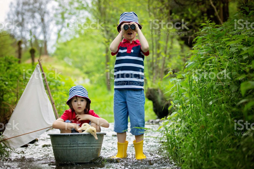 Cute children, boy brothers, playing with ducks on a little river. Kids having fun, childhood happiness concept stock photo