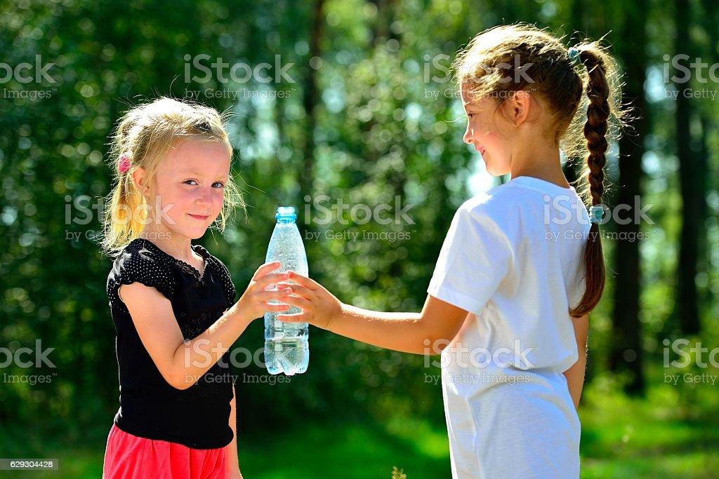 Cute children drinking water from a bottle Стоковые фото Стоковая фотография
