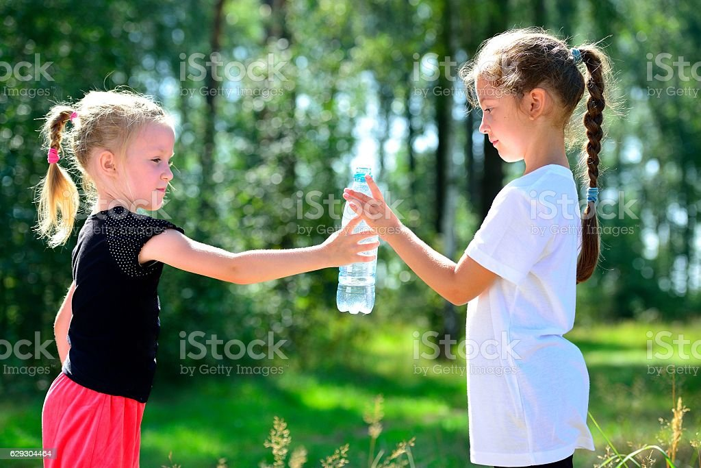 Cute children drinking water from a bottle стоковое фото