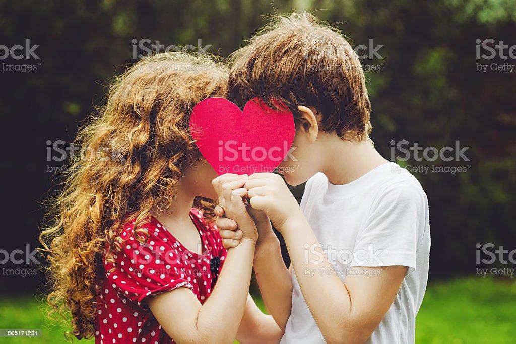 Cute children holding red heart shape in summer park. stock photo