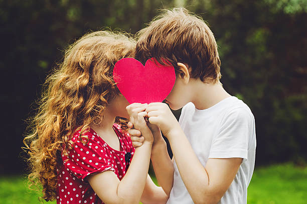 Cute children holding red heart shape in summer park. stock photo