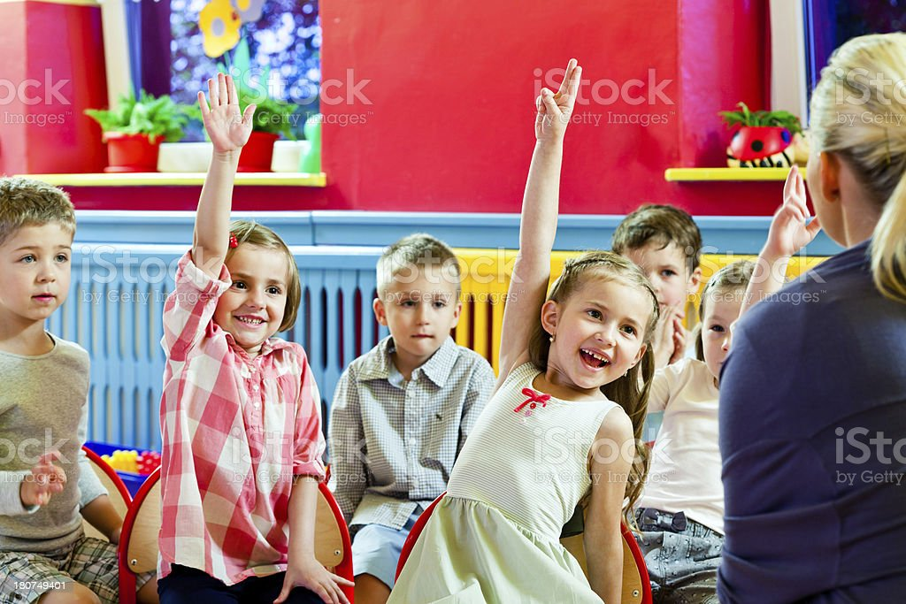 Cute Children in Nursery School A happy preschool children sitting in a row in a classroom and answering teacher's questions. 4-5 Years Stock Photo