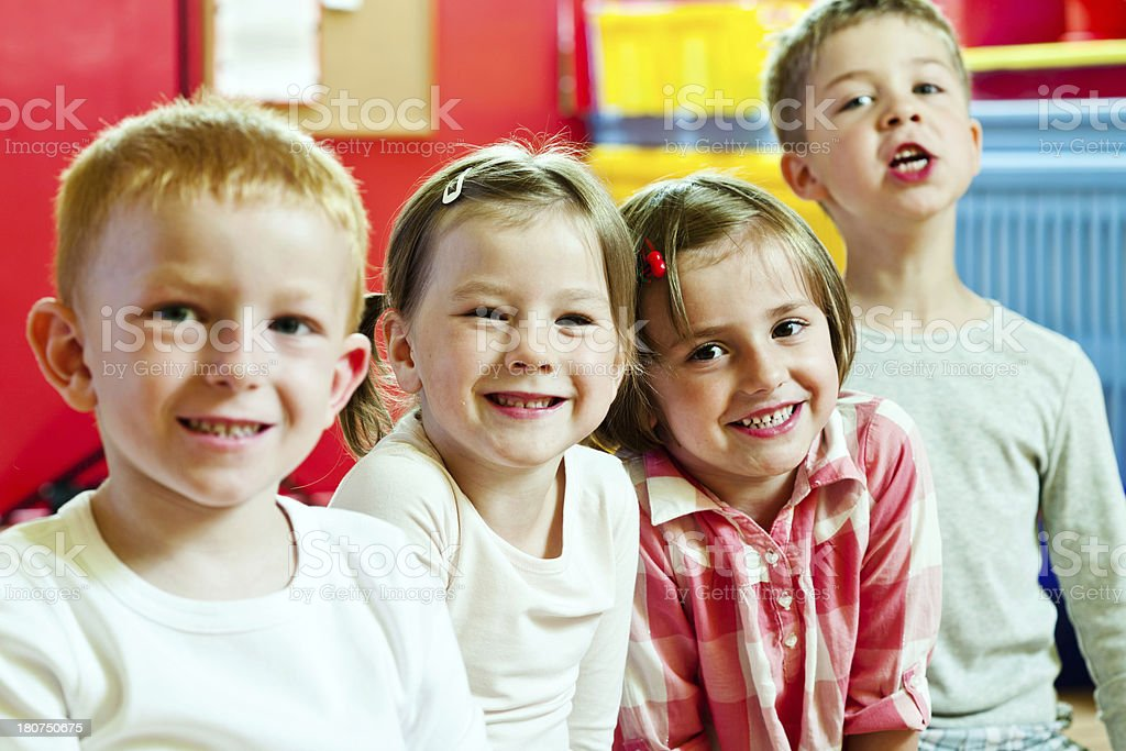 Cute Children in Nursery School A happy preschool children sitting in a row in a classroom and laughing at camera. 4-5 Years Stock Photo