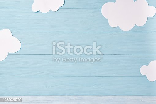 1090975842 istock photo Cute children or baby background, white clouds on the blue wooden background 1085026792