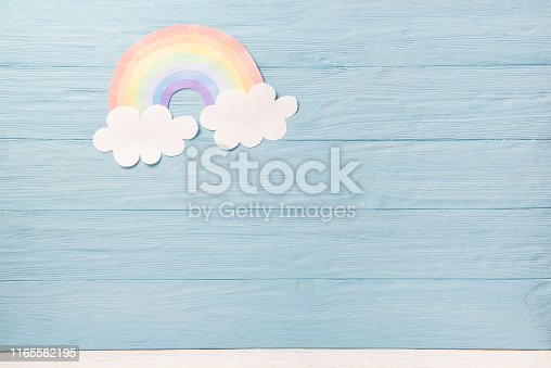 677933036 istock photo Cute children or baby background, white clouds with rainbow on the blue wooden background 1165582195