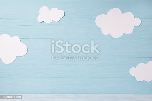 1090975842 istock photo Cute children or baby card, white clouds on the blue wooden background 1085024738