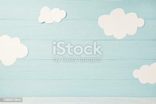 istock Cute children or baby card, white clouds on the light blue wooden background, tonned 1090975842