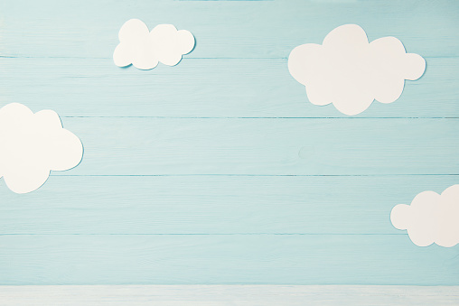 Cute children or baby card with white clouds on the light blue wooden background, toned