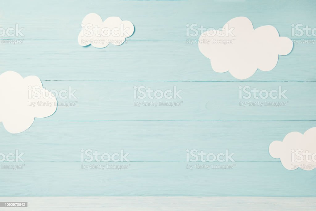 Cute children or baby card, white clouds on the light blue wooden background, tonned stock photo