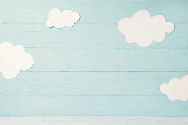 cute children or baby card, white clouds on the light blue wooden background, tonned - infanzia foto e immagini stock