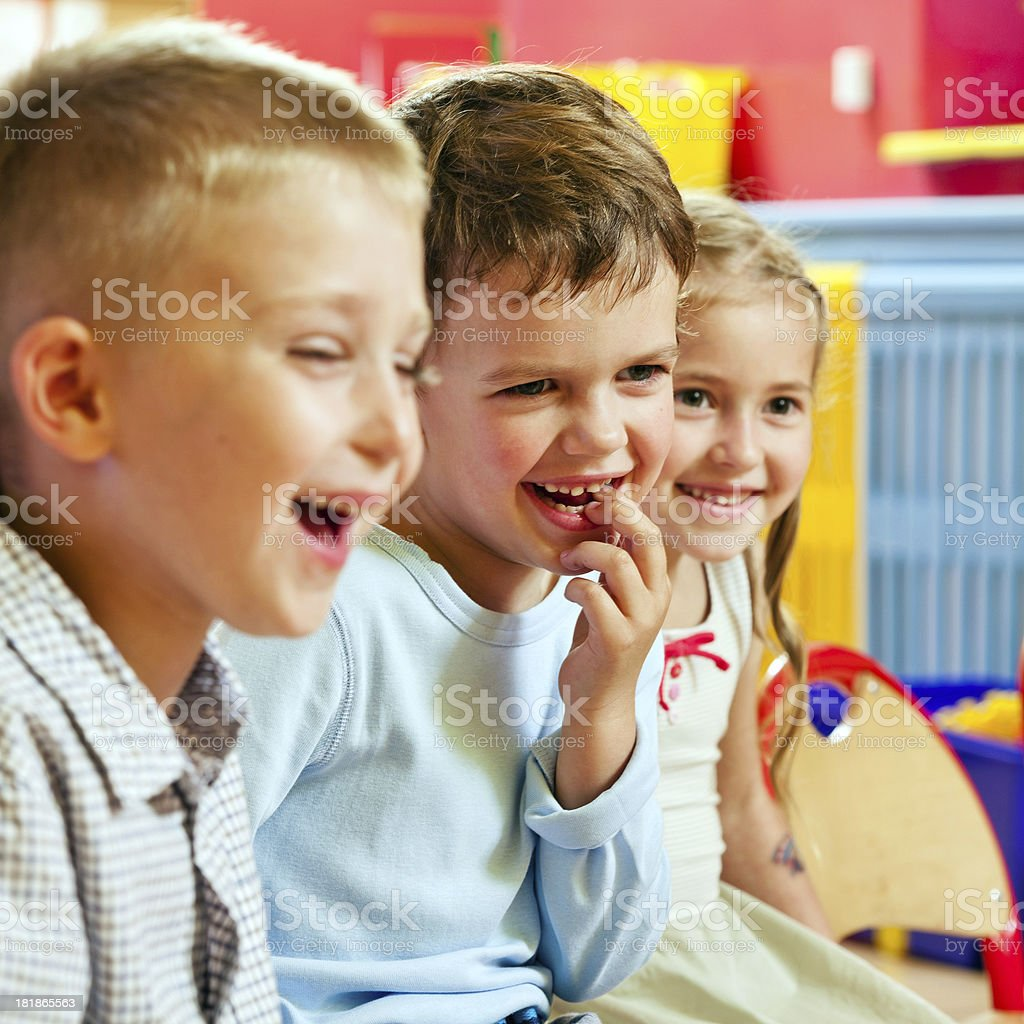 Cute Children A happy preschool children sitting in a row in a classroom and laughing. 4-5 Years Stock Photo