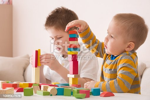657779378 istock photo Cute children playing with colorful wooden bricks on the white table at home. Toddler and kid boy building tower with geometric shapes. Learning and education concept. 1058907526