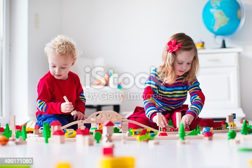 istock Cute children playing with toy railroad and train 499171080