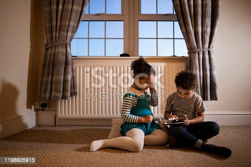 Two siblings playing on a mobile phone together while sitting in a room on the floor.