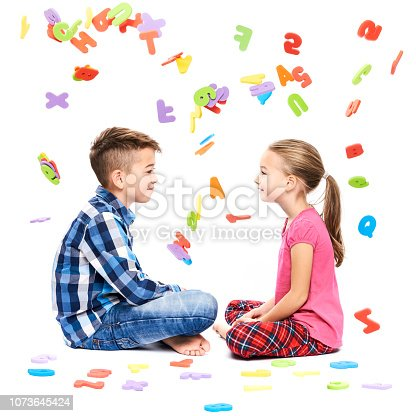 istock Cute children with large colorful alphabet letters on white background. Kids speech therapy concept. Speech impediment, logopedy background. 1073645424