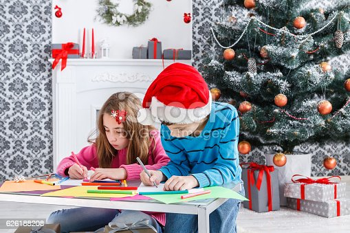 1062609644istockphoto Cute children writing letter to santa, wait for christmas 626188208