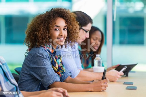 istock Cute college girl taking notes in class using smart phone 532850009