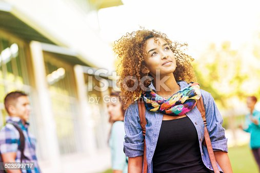 istock Cute college student walking around campus on sunny day 523599717