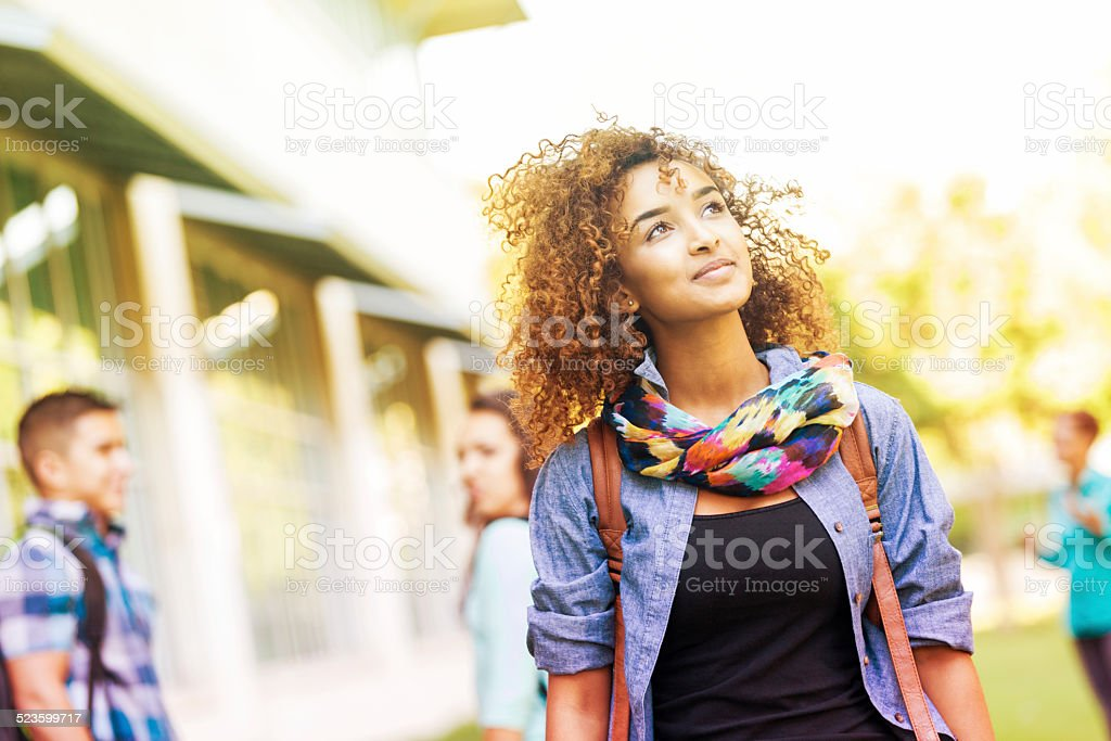 Cute college student walking around campus on sunny day stock photo