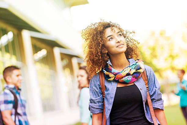 mignon collège étudiants marchant dans campus sur belle journée ensoleillée - vie étudiante photos et images de collection