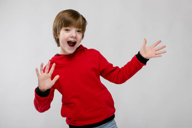 Cute confident caucasian little boy in red sweater showing open palm with open mouth on grey background stock photo