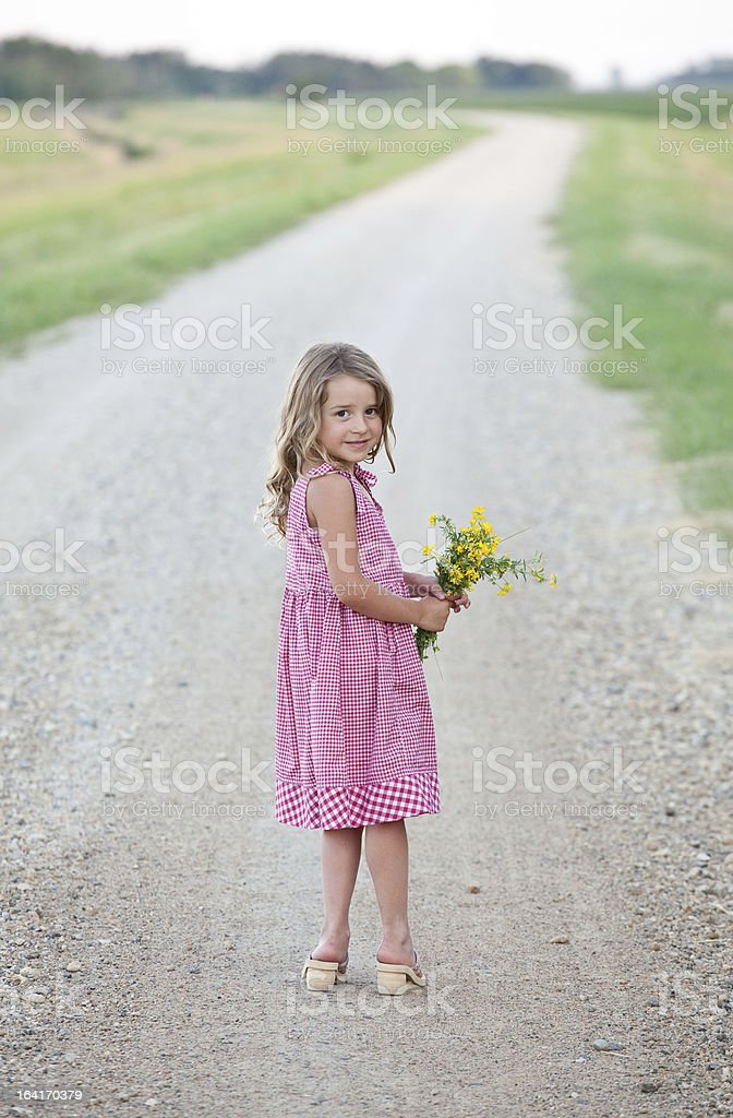 Cute Country Girl on Gravel Road Holding Flowers royalty-free stock photo