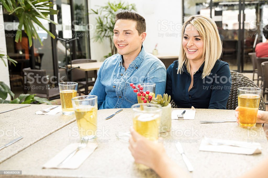 Cute couple drinking with some friends stock photo