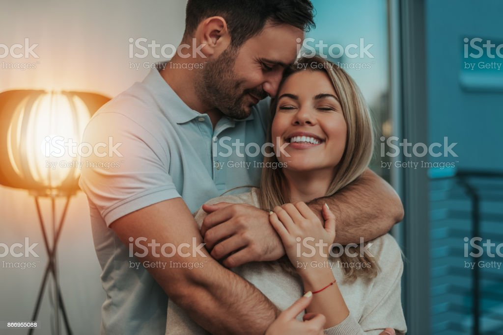 Cute Couple Hugging And Smiling In Their New Home Stock Photo Download Image Now Istock