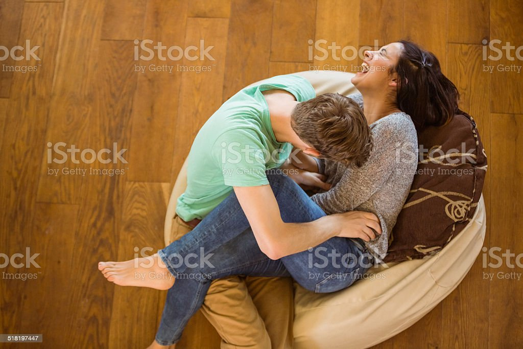 Cute couple laughing together on beanbag stock photo