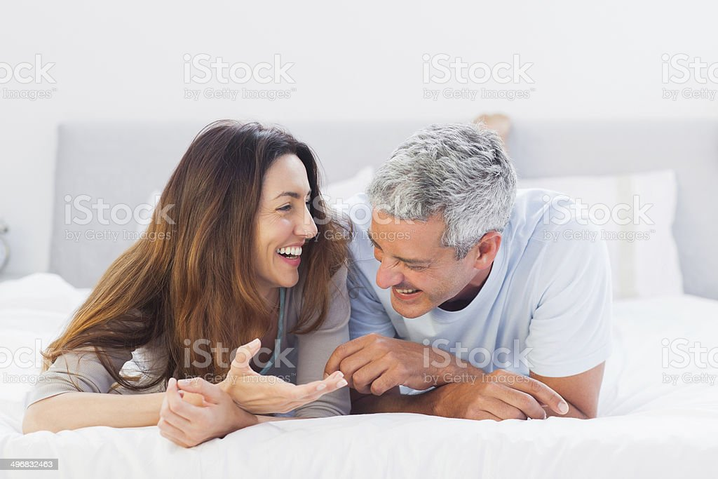 Cute couple lying on bed talking together stock photo