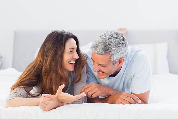 cute couple lying on bed talking together - mid volwassen koppel stockfoto's en -beelden