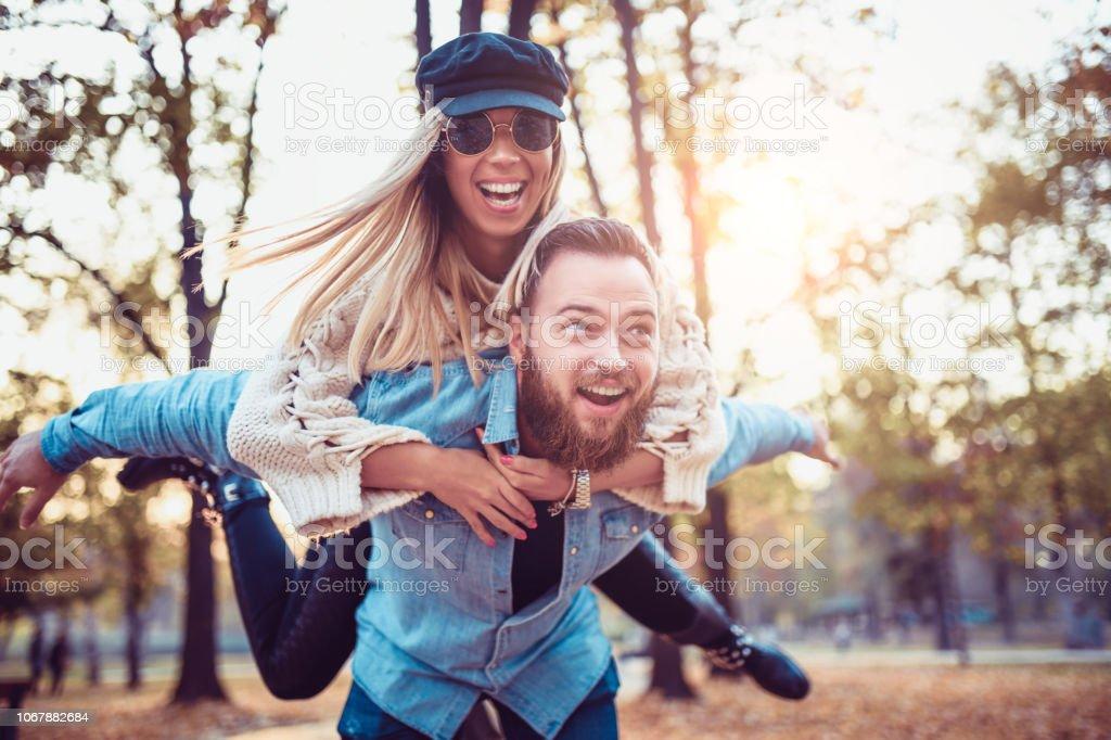 Cute Couple Make Piggyback Ride In Public Park stock photo