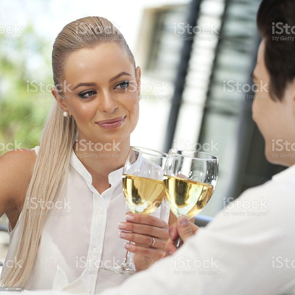 Cute couple making a toast with white wine, royalty-free stock photo