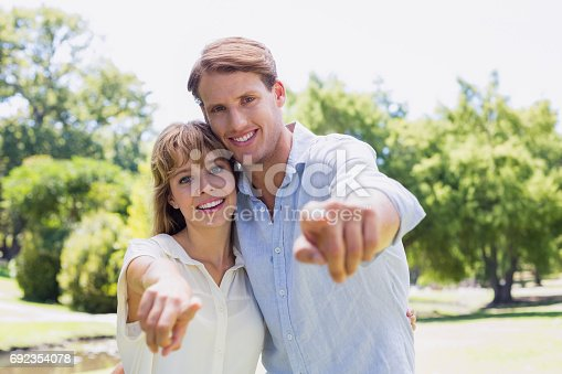 Cute couple pointing to the camera in the park on a sunny day