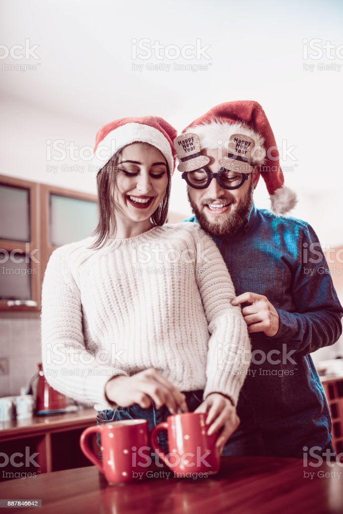 cute couple preparing hot drink for themselves at christmas morning royalty free stock photo