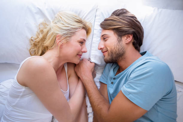 Cute couple relaxing on bed smiling at each other stock photo