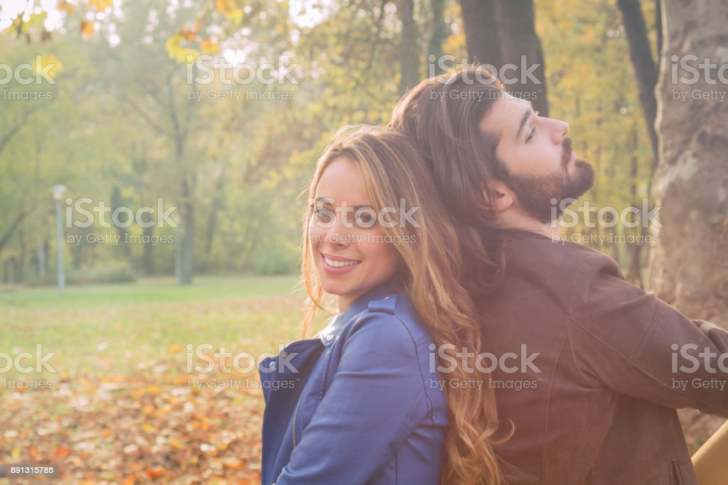 Cute couple sitting on a bench in park filled with autumn colors. stock photo