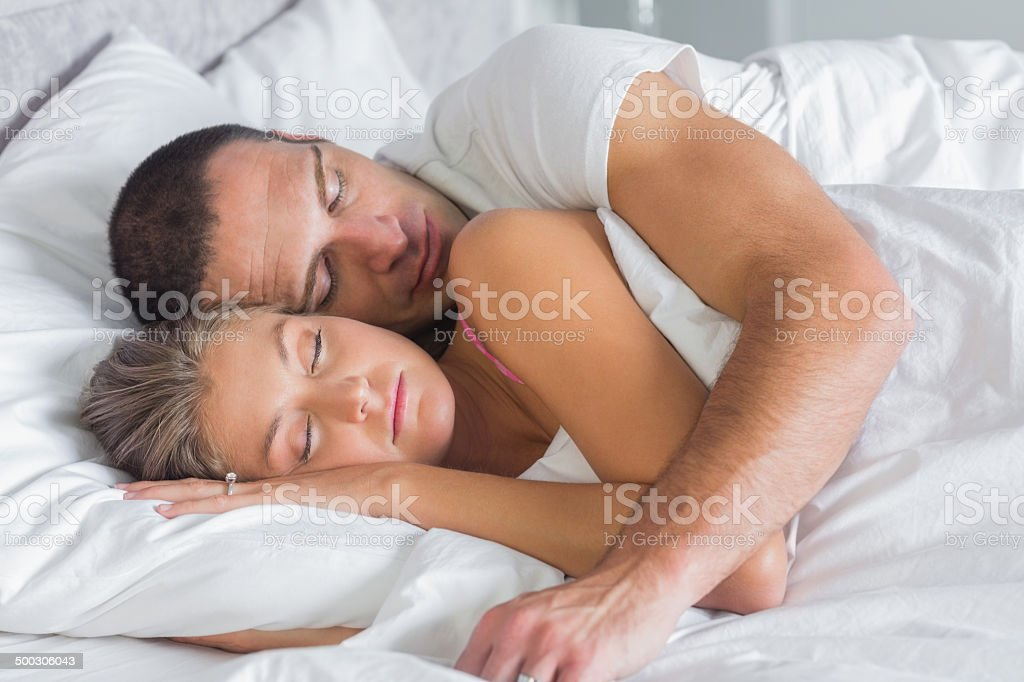 Cute couple sleeping and cuddling in bed stock photo